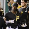 Photo - Pittsburgh Pirates' Andrew McCutchen, center, celebrates with teammates in the dugout after hitting a two-run home run off Chicago Cubs starting pitcher Jason Hammel during the first inning of a baseball game in Pittsburgh Wednesday, June 11, 2014. (AP Photo/Gene J. Puskar)