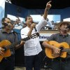 Photo - Ecuador's President Rafael Correa, center, sings with a band before the start of his his weekly broadcast