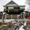 A small home damaged by Superstorm Sandy is braced in the air Tuesday, Feb. 5, 2013, in Union Beach, N.J., as workers raise it to prevent future flooding. New Jersey Gov. Christie told a gathering in Union Beach Tuesday that the National Flood Insurance Program\'s handling of claims in New Jersey