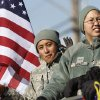 Members of the 34th Combat Communication Squadron at Tinker AFB ride in the back of military trucks during the parade. The city of Midwest City teamed with civic leaders and local merchants to display their appreciation for veterans and active military forces by staging a hour-long Veteran\'s Day parade that stretched more than a mile and a half along three of the city\'s busiest streets Monday morning, Nov. 12, 2012. Hundreds of people lined the parade route, many of them waving small American flags that had ben distributed by volunteers who marched near the front of the parade. A fly-over performed by F-16s from the138th Fighter Wing, Oklahoma Air National Guard unit in Tulsa thrilled spectators. Five veterans representing military personnel who served in five wars and military actions served as Grand Marshals for the parade. Leading the parade was the Naval Reserve seven-story American flag, carried by 100 volunteers from First National Bank of Midwest City, Advantage Bank and the Tinker Federal Credit Union. The flag is 50 feet by 76 feet, weighs 110 pounds and was sponsored by the MWC Chapter of Disabled American Veterans. Photo by Jim Beckel, The Oklahoman