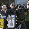 """Miles Scott, dressed as Batkid, second from left, raises his arm next to Batman at a rally outside of City Hall with Mayor Ed Lee, left, and his father Nick and brother Clayton, at right, in San Francisco, Friday, Nov. 15, 2013. Scott was called into service on Friday morning by San Francisco Police Chief Greg Suhr to help fight crime, as San Francisco turned into Gotham City as city officials helped fulfill the 5-year-old leukemia patient\'s wish to be """"Batkid,"""" The Greater Bay Area Make-A-Wish Foundation says. He was diagnosed with leukemia when he was 18 months old, finished treatment in June and is now in remission, KGO-TV reported. (AP Photo/Jeff Chiu)"""