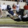Photo - Mississippi quarterback Bo Wallace, left, dives over Vanderbilt safety Andrew Williamson (32) for a touchdown on a 3-yard run in the third quarter of an NCAA college football game on Thursday, Aug. 29, 2013, in Nashville, Tenn. (AP Photo/Mark Humphrey)