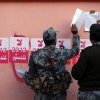 Egyptian military officers hang the list of voters names next to stickers with Arabic writing that reads