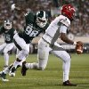 Photo - Michigan State defensive end Demetrius Cooper (98) chases Jacksonville State quarterback Eli Jenkins (7) during the first half of an NCAA college football game in East Lansing, Mich., Friday, Aug. 29, 2014. (AP Photo/Paul Sancya)