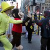 A man in a spider sweatshirt does a high-five with characters The Man in the Yellow Hat and Curious George outside the Nasdaq MarketSite, before the Houghton Mifflin IPO, in New York\'s Times Square, Thursday, Nov. 14, 2013. (AP Photo/Richard Drew)