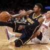 Photo - Indiana Pacers' Paul George, left, passes the ball after tumbling to the court with New York Knicks' Jason Kidd during the first half of the NBA basketball game, Sunday, April 14, 2013, in New York. (AP Photo/Seth Wenig)
