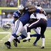 Indianapolis Colts\' Ricardo Mathews (91) looses his helmet as he tackles Houston Texans\' Arian Foster (23) during the first half of an NFL football game, Sunday, Dec. 30, 2012, in Indianapolis. (AP Photo/AJ Mast)