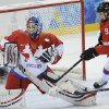 Photo - Goalkeeper Anna Prugova of Russia grabs the puck under pressure from Stefanie Marty of Switzerland during the 2014 Winter Olympics women's ice hockey quarterfinal game at Shayba Arena, Saturday, Feb. 15, 2014, in Sochi, Russia. (AP Photo/Matt Slocum)