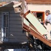A resident removes kitchen items from a cabinet in a tornado-damaged home in Century, Fla., Tuesday, Feb. 16, 2016. (AP Photo/Michael Snyder)