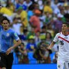 Photo - Uruguay's Edinson Cavani, left, celebrates as he runs past Costa Rica's Cristian Gamboa after scoring the opening goal during the group D World Cup soccer match between Uruguay and Costa Rica at the Arena Castelao in Fortaleza, Brazil, Saturday, June 14, 2014.  (AP Photo/Bernat Armangue)