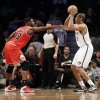 Brooklyn Nets\' Jason Collins, right, takes a shot over Chicago Bulls\' Nazr Mohammed during the second half of an NBA basketball game Monday, March 3, 2014, in New York. The Nets won 96-80. (AP Photo/Seth Wenig)