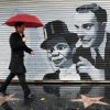 Photo - A pedestrian passes by a mural showing iconic comedy team Charlie McCarthy and  Edgar Bergan during a rainstorm in the Hollywood section of Los Angeles Friday, Nov. 30, 2012. A series of storm systems will continue to move across southwestern California through Monday morning. (AP Photo/Damian Dovarganes)