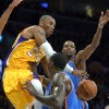 Photo - Los Angeles Lakers guard Kobe Bryant, left, passes between Oklahoma City Thunder forward Kevin Durant, back, and center Kendrick Perkins during the first half of their NBA basketball game, Friday, Jan. 11, 2013, in Los Angeles. (AP Photo/Mark J. Terrill) ORG XMIT: LAS107