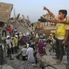 Bangladeshi rescuers from a youth group gesture for help at the site of a building that collapsed Wednesday in Savar, near Dhaka, Bangladesh, Thursday, April 25, 2013. By Thursday, the death toll reached at least 194 people as rescuers continued to search for injured and missing, after a huge section of an eight-story building that housed several garment factories splintered into a pile of concrete.(AP Photo/Kevin Frayer)
