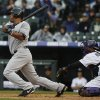 New York Yankees\' Vernon Wells, left, hits an RBI-single as Colorado Rockies catcher Wilin Rosario looks on during the first inning of a baseball game in Denver on Thursday, May 9, 2013. (AP Photo/David Zalubowski)