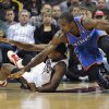 Milwaukee Bucks\' Khris Middleton, left, and Oklahoma City Thunder\'s Serge Ibaka scramble for a loose ball during the second half of an NBA basketball game Saturday, Nov. 16, 2013, in Milwaukee. The Thunder defeated the Bucks 92-79. (AP Photo/Jim Prisching)