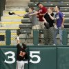 A fan uses his cap to catch a home-run ball by West Virginia\'s Brady Wilson (23) (not pictured) as Oklahoma State\'s Gage Green tries to to make the catch in the sixth inning during an NCAA baseball game between Oklahoma State and West Virginia in the Big 12 Baseball Championship tournament at the Chickasaw Bricktown Ballpark in Oklahoma City, Saturday, May 25, 2013. The home run tied the game at 5-5. WVU beat OSU 6-5 in ten innings. Photo by Nate Billings, The Oklahoman
