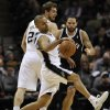 Photo - San Antonio Spurs guard Tony Parker, front, of France, recovers after colliding with Brooklyn Nets guard Deron Williams during the first half of an NBA basketball game on Tuesday, Dec. 31, 2013, in San Antonio. (AP Photo/Darren Abate)