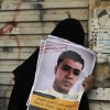 Photo - A Bahraini mourner holds up posters of an anti-government protester during his funeral procession in Sanabis in the suburbs of the capital of Manama, Bahrain, Sunday, July 6, 2014. Abdel Aziz al-Abbar, 27, died in April after being shot in the head during a protest earlier in the year. His body was released for burial after authorities agreed to his family's demand to specify he was shot in the official cause of death. (AP Photo/Hasan Jamali)