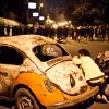 In this Monday, Jan. 28, 2013 photo, an Egyptian protester take cover beside a vehicle damaged during clashes between protesters and Egyptian security forces in Downtown Cairo, Egypt. On Tuesday, Jan. 29, 2013, Egypt\'s army chief warns of