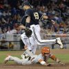 Photo - Texas' Madison Carter, bottom, tries to avoid the tag by sliding into first base but is out by Vanderbilt first baseman Zander Wiel (43) in the ninth inning of an NCAA baseball College World Series game in Omaha, Neb., Saturday, June 21, 2014. (AP Photo/Ted Kirk)