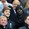 Photo - Liverpool's Adam Lallana, left, and Mario Balotelli in the stands during the English Premier League match at the Etihad Stadium, Manchester, where Manchester City were playing Liverpool, Monday Aug. 25, 2014. (AP Photo/PA, Peter Byrne)  UNITED KINGDOM OUT  NO SALES  NO ARCHIVE