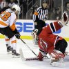 Philadelphia Flyers\' Claude Giroux, left, scores on New Jersey Devils goalie Martin Brodeur during the first period of Game 4 of a second-round NHL hockey Stanley Cup playoff series, Sunday, May 6, 2012, in Newark, N.J. (AP Photo/Julio Cortez)