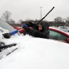 Tiffany Collins removes snow from her windshield as rain and sleet continues to fall in downtown Evansville, Ind., Tuesday, Feb. 4, 2014. A Winter Storm Warning was issued Tuesday as a mixture of snow, sleet and rain continued into the evening with temperatures around 30 degrees. (AP Photo/The Evansville Courier & Press, Jason Clark)