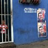 Santiago, 2, peeks out from the gate on his home\'s doorway where posters of Venezuela\'s President Hugo Chavez cover a wall in Caracas, Venezuela, Friday, Oct. 5, 2012. Venezuelans will head to the polls Sunday to vote in their country\'s presidential election, deciding on whether to keep Chavez or seek change. (AP Photo/Rodrigo Abd)