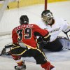 Photo - Anaheim Ducks goalie Jonas Hiller, right, from the Czech Republic, lets in a goal from Calgary Flames' TJ Galiardi during the first period of an NHL hockey game in Calgary, Alberta, Wednesday, March 12, 2014. (AP Photo/The Canadian Press, Jeff McIntosh)