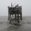 Residents carry their belongings up their house on stilts as strong winds and rains caused by Typhoon Koppu hits the coastal town of Navotas, north of Manila, Philippines on Sunday, Oct. 18, 2015. Slow-moving Typhoon Koppu blew ashore with fierce wind in the northeastern Philippines early Sunday, toppling trees and knocking out power and communications. (AP Photo/Aaron Favila)