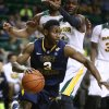 Photo - West Virginia guard Juwan Staten (3) drives past Baylor guard Gary Franklin (4) in the first half of an NCAA college basketball game, Tuesday, Jan. 28, 2014, in Waco, Texas. (AP Photo/Waco Tribune Herald, Rod Aydelotte)