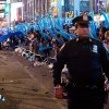 FILE - In this Dec. 31, 2011 file photo, a police officer walks through a frozen zone in New York City's Times Square as revelers wave balloons in anticipation of midnight. The New York City police use an array of security measures for the event that turns the