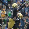 Photo - Notre Dame quarterback Everett Golson, right, holds up wide receiver Amir Carlisle in the end zone after Golson's third running touchdown during an NCAA college football game with Rice in South Bend, Ind., Saturday, Aug. 30, 2014. Notre Dame won 48-17. (AP Photo/Joe Raymond)