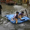 Indian children play on a water logged street in Kolkata, India, Saturday, Aug. 1, 2015. Cyclonic storm Komen weakened into a depression after making landfall over Bangladesh coast on Thursday, causing heavy rainfall in several parts of the eastern Indian state of West Bengal and throwing normal life out of gear as most parts of the city were submerged, according to local reports. (AP Photo/Bikas Das)