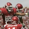 OU: University of Oklahoma wide receiver Ryan Broyles, left, celebrates a touchdown against Cincinnati with teammate Juaquin Iglesias, right, in front of quarterback Sam Bradford, center, in the first quarter of an NCAA college football game in Norman, Okla., Saturday, Sept. 6, 2008. (AP Photo/Sue Ogrocki) ORG XMIT: OKSO109