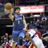 Photo - Minnesota Timberwolves guard Ricky Rubio (9), of Spain, passes off the ball against Washington Wizards guard John Wall (2) during the first half of an NBA basketball game on Friday, Jan. 25, 2013, in Washington. (AP Photo/Nick Wass)