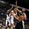 Oklahoma City\'s Russell Westbrook (0) passes the ball as San Antionio\'s Bruce Bowen (12) , left, and Tim Duncan (21) defend him during the NBA game between Oklahoma City and San Antonio, Tuesday April 7, 2009, at the Ford Center in Oklahoma CIty. Photo by Sarah Phipps, The Oklahoma