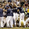 Photo - Milwaukee Brewers' Jonathan Lucroy celebrates with teammates after hitting a walk off home run during the ninth inning of a baseball game against the Cincinnati Reds Tuesday, July 22, 2014, in Milwaukee. The Brewers won 4-3. (AP Photo/Morry Gash)