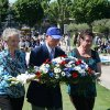 Photo - Gerry Correll, left, of Ponca City, and her sister, Shirley Awalt, right, of Elk Grove, Calif., are escorted by Maurice Dreclerc, president of the Le Souvenir Franco-Americain (Franco-American Society of Draguignan) as they place a wreath during ceremonies at Rhone American Cemetery.  PHOTO PROVIDED BY THE Franco-American Society/American Battle Monuments Commission