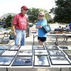 Photo - Bob Rice shows Lisa Doan items for sale in his driveway during the three-day citywide garage sale in Norman. PHOTO BY STEVE SISNEY, THE OKLAHOMAN <strong>STEVE SISNEY</strong>