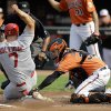 Photo - Baltimore Orioles catcher Caleb Joseph, right, tags out St. Louis Cardinals' Matt Holliday in the first inning of an interleague baseball game, Saturday, Aug. 9, 2014, in Baltimore. (AP Photo/Patrick Semansky)