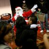 Photo -  Santa Claus waves to kindergarten students while high school students pass out gifts during the annual Christmas Party and gift exchange at Santa Fe South High School in OKlahoma City on Friday, Dec. 3, 2010. Photo by John Clanton, The Oklahoman