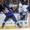 Photo - Vancouver Canucks' Mike Santorelli (25) and St. Louis Blues' Jay Bouwmeester (19) battle for the puck during the first period of an NHL hockey game on Friday, Oct. 25, 2013, in St. Louis. (AP Photo/Bill Boyce)