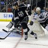 Photo - Los Angeles Kings defenseman Slava Voynov (26), of Russia, clears the puck and is chased by San Jose Sharks center Patrick Marleau (12) in the first period of an NHL hockey game in Los Angeles Saturday, April 27, 2013. (AP Photo/Reed Saxon)