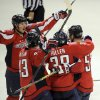 Photo - Washington Capitals defenseman Mike Green (52) celebrates his goal with Jack Hillen (38), Tom Wilson (43) and Nicklas Backstrom, left, during the third period of an NHL hockey game against the Vancouver Canucks, Friday, March 14, 2014, in Washington. The Capitals won 4-3. (AP Photo/Nick Wass)