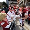 Austin Woods (50) signs autographs as fans line up behind him wating to enter the field for player autographs after the annual Spring Football Game at Gaylord Family-Oklahoma Memorial Stadium in Norman, Okla., on Saturday, April 13, 2013. Photo by Steve Sisney, The Oklahoman