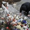 A woman pays respects at a memorial outside of St. Rose of Lima Roman Catholic Church, Sunday, Dec. 16, 2012, in Newtown, Conn. On Friday, a gunman allegedly killed his mother at their home and then opened fire inside the Sandy Hook Elementary School in Newtown, killing 26 people, including 20 children. (AP Photo/Julio Cortez) ORG XMIT: CTJC119