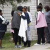 Photo - Family and friends console each other outside 7318 Enchanted Creek in Cypress, Texas, Sunday, Nov. 10, 2013, after two people were killed and at least 22 others were injured Saturday night when gunfire rang out at a large house party in a Houston suburb, sending partygoers fleeing in panic, authorities said. Authorities say they're seeking two gunmen. (AP Photo/Bob Levey)