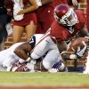Oklahoma\'s Durron Neal (5) stretches for extra yardage as he is tackled by TCU\'s Sam Carter (17) during a college football game between the University of Oklahoma Sooners (OU) and the TCU Horned Frogs at Gaylord Family-Oklahoma Memorial Stadium in Norman, Okla., on Saturday, Oct. 5, 2013. Photo by Steve Sisney, The Oklahoman